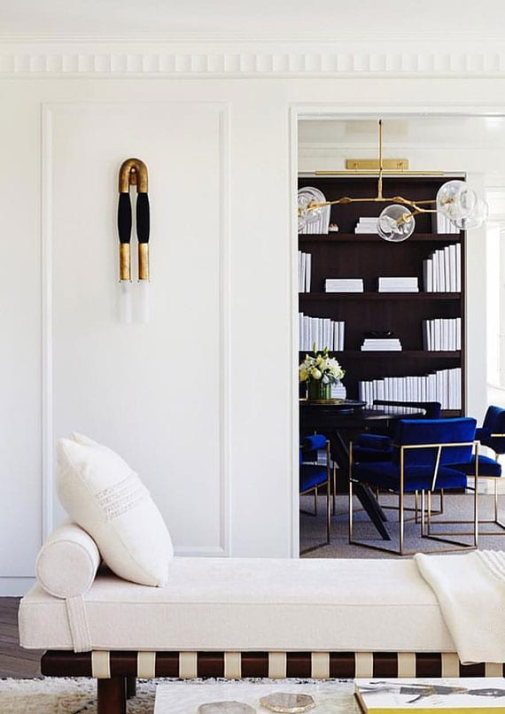 elegante raumgestaltung in weiß mit rundem holztisch schwarz, blauen T Back Lounge Stühlen, moderner wandleuchte aus messing in gold und schwarzem pferdehaar, einbau-bücherregal aus holz, modernem tagesbett holz