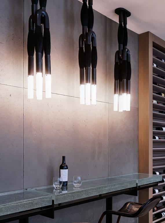 coole weinkeller idee für moderne einrichtung mit holzweinregalen, bartisch aus metall und glas mit schwarzen lederbarstühlen,betonwandpaneelen und modernen pendellampen aus pferdehaar schwarz