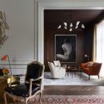attraktive raumdekoration mit rundem wandspiegel in abstraktem goldrahmen und schwarzweißer fotografie einer frau, elegante raumgestaltung mit barock-stühl in schwarzem leder, modernem beistelltisch gold, retro seats and sofa in orange und beige, wandfarbe braun