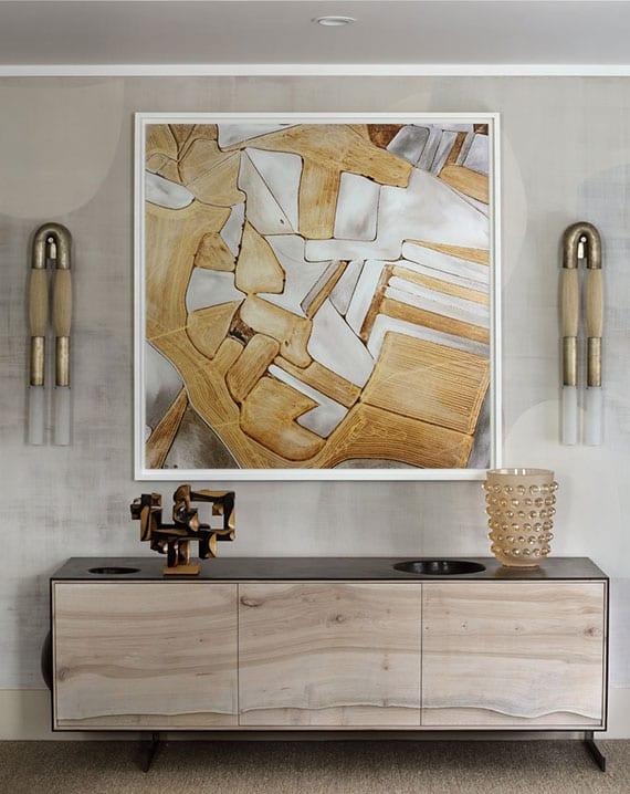 stilvolle wohnzimmereinrichtung mit modernem sideboard in holz und schwarz und coole wandgestaltung mit wandfarbe grau, abstraktem gemälde zwischen gewölbten wandleuchten aus messing und pferdehaar