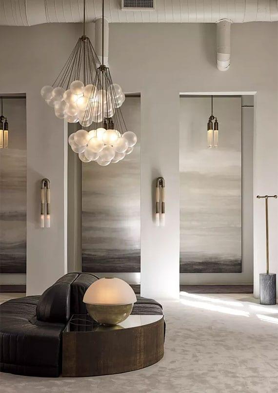 modernes wohnzimmer mit weißem teppichboden, rundem ledersofa schwarz, eckbeistelltisch mit kugel-tischlampe, offenem flur mit großen gemälden als wanddeko, wolken-pendellampen und modernen wandleuchten aus metall und pferdehaar
