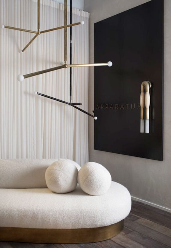 moderne wohnzimmer ideen für attraktive raumgestaltung mit einzigartigen leuchten aus messing, wanddeko mit schwarzem wandpaneel, kuscheligem polstersofa weiß auf dunklem holzboden und weißen gardinen