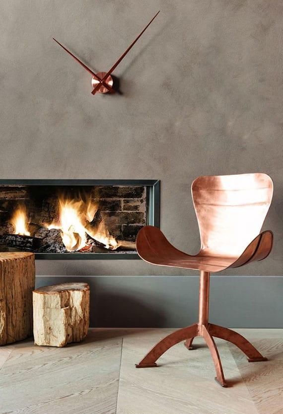 wohnzimmer modern gestalten mit kupferstuhl und feuerholz auf hellem parkettboden, wandfarbe cappuccino, regal aus grauem metall und moderner wanduhr kupfer
