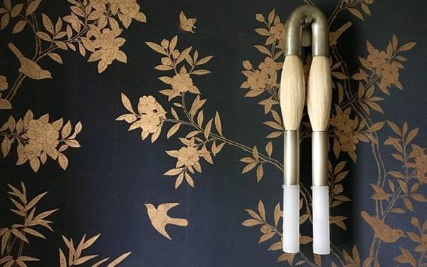coole wandgestaltung idee mit modernen wandleuchten aus messing und pferdehaar und schwarzer wandtapette mit goldenem blumenmuster