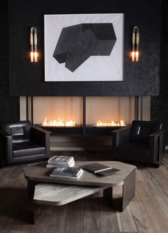 elegantes maskulines interieur in schwarz mit offenem kamin, ledersesseln, couchtisch aus holz und metall, schlichte wanddeko mit gewölbten wandleuchten aus messing und pferdehaar