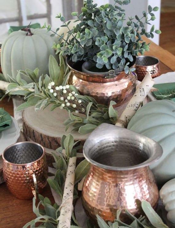 tisch herbstlich und rustikal eindecken mit kürbissen und grünen pflanzen auf holzscheiben und kupfertassen