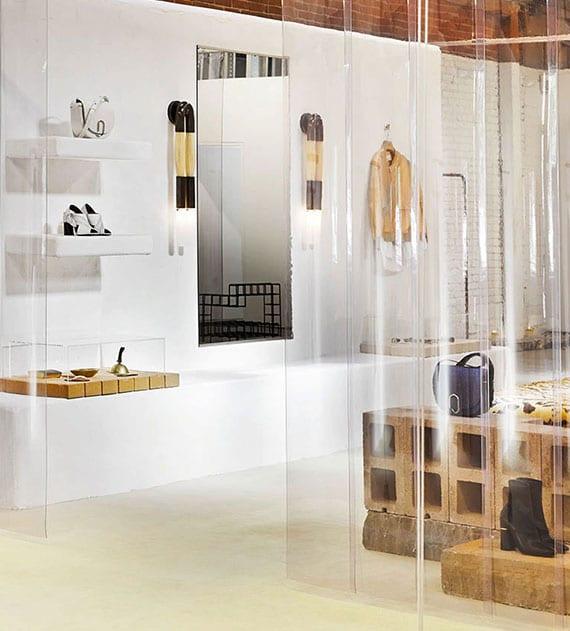 kreatives interieur design vom modedesign laden mit weißen wänden, ausgemauerten wandregalen, transparentem vorhang, ziegeländen, ganzkürperspiegel mit schwarzen wandlampen aus messing und pferdehaar