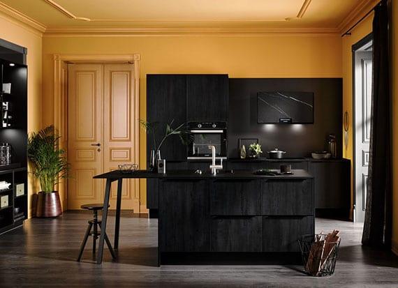 attraktive küchengestaltung in schwarz und gelb mit kleiner trendküche in schwarzer Natursteinoptik und Kücheninsel mit Esstisch