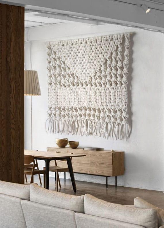 attraktive makramee-wanddeko und moderne wohnzimmergestaltung mit sideboard und essgruppe aus holz in klassischem stil