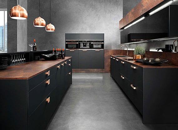 schicke kücheneinrichtung mit trendküche in schwarz und kupfer mit betonboden, einbauküchengeräten schwarz, pendellampen kupfer, spiegel-spritzwand und kücheninsel