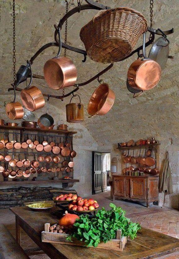 rustikale küchengestaltung im landhausstil mit pflasterboden, massibholztisch, diy wandregal holz, bogendach und kupfergeschirr