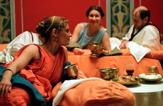 Gastmahl im römischen Speisesaal mit drei speisesofas und rundem esstisch