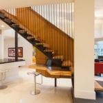moderne gerade treppe aus stahl und holz mit büroschreibtisch holz darunter als platzsparende treppenlösung für offenne wohzimmer mit küche und homeoffice