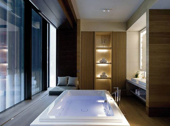 luxuriöse badezimmergestaltung mit freistehender whirlpool-badewanne, waschtisch naturstein mit zwei waschbecken, beleuchtetem wandspiegel und regal für badetücher, einbau wandregal holz mit indirekter beleuchtung