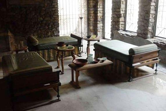 typischer Speisesaal aus der Antike mit liegesofas aus holz und holzbeistelltischen