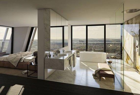 luxus schlafzimmer mit offenem bad und panoramablick auf die stadt_traumbad gestatung mit freistehender badewanne, spiegelwandschrank, regenschauerdusche hinter glaswand und waschtischschrank mit zwei runden waschbecken