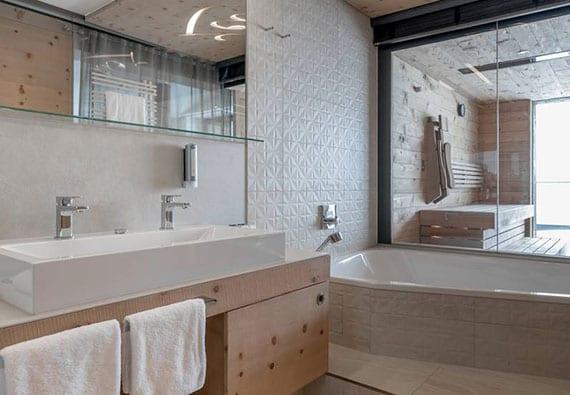 stilvolles bad einrichten mit holzwaschtisch, doppel-aufsatzwaschtisch, badspiegel mit regal, badewanne mit glaswand zur sauna und weißen wandfliesen in 3d-optik
