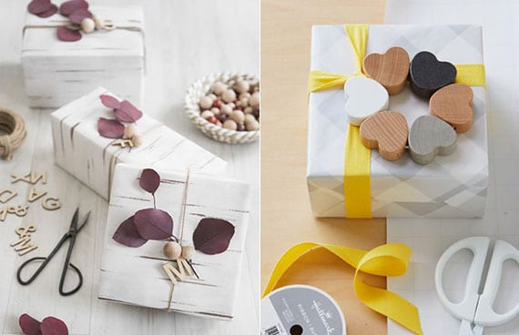 Geschenke Verpackung mit weißem Geschenkpapier, Holzkugeln und Holzbuchstaben, dunkelroten Eukalyptuszweigen, gelbem Geschenkband und kranz aus holzherzen