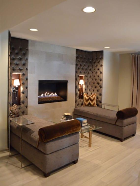 gemütliche sitzecke im wohnzimmer einrichten mit zwei Liegesofas in beige, couchtisch glas, einbaukamin, wandlampen und wandpolster braun