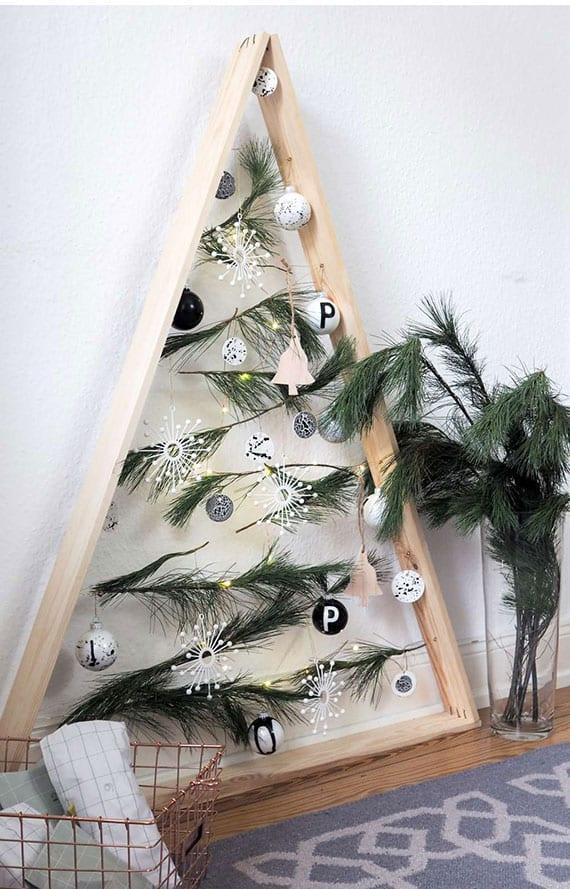 christbaum als moderne weihnachtsdeko basteln aus holz, nadelzweigen und christbaumkugeln in weiß und schwarz