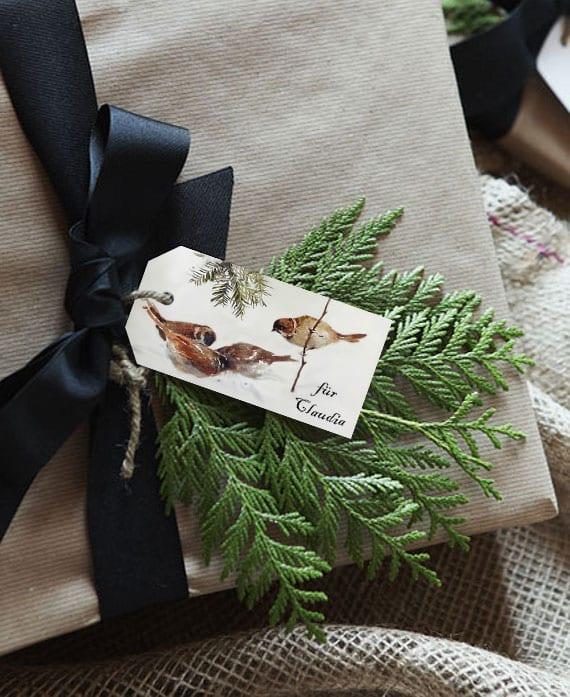 coole weihnachtsgeschenkverpakung mit altpapier, schwarzer stoffband, immergrünzweigen und DIY Geschenkkarte mit Wintervögeln