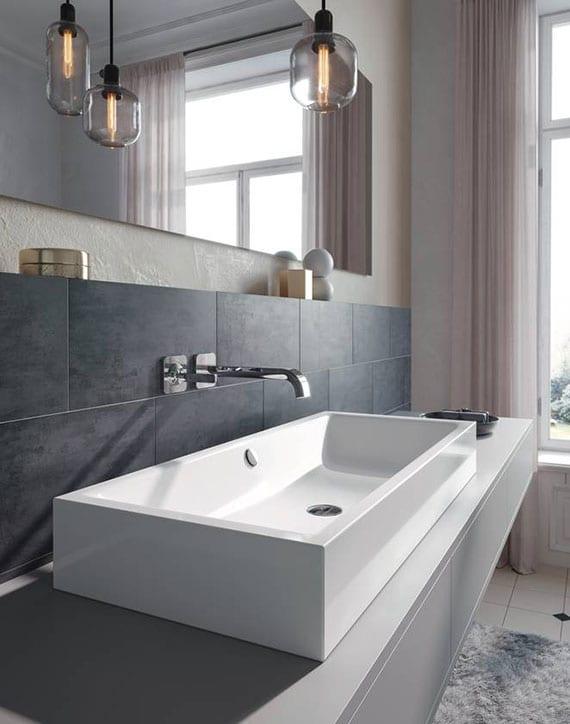 stilvolle gestaltungsideen für traumbad mit grauen badfliesen, modernen Pendellampen vor länglichem wandspiegel,modernem waschtisch grau mit rechteckigem aufsatzwaschbecken