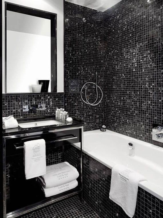 ein kleines bad modern gestalten mit schwarzer mosaik, badewanne mit dusche und wandspiegel über modernem möbelwaschtisch in schwarz mit regal, schublade und handtuchhalter