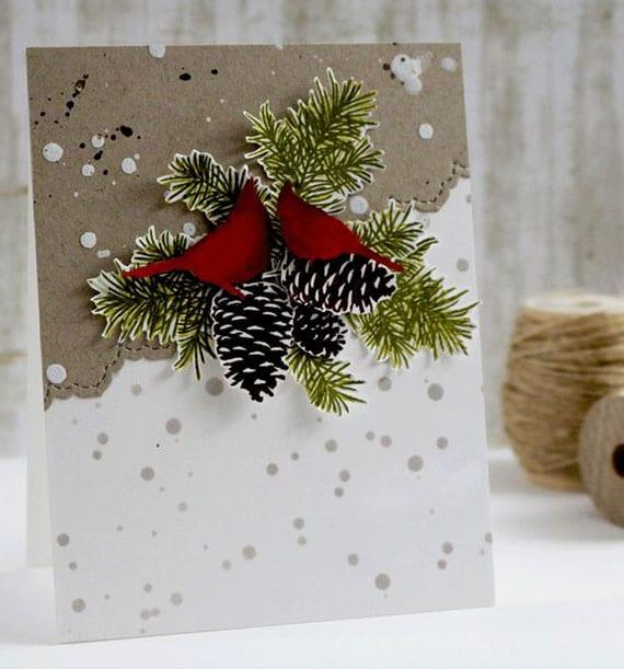festliche Weihnachtskarte diy aus weißem und braunen karton mit roten vögeln, nadelbaumzweigen und zafpgen