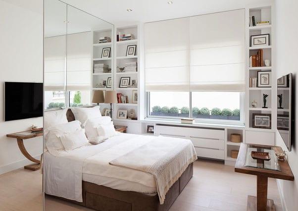 kleines schlafzimmer modern und hell einrichten mit einbau-bücherregalen, tv an der wand, spiegelwand hinterm boxspringbett mit kopfteil und holzbeistelltisch antik