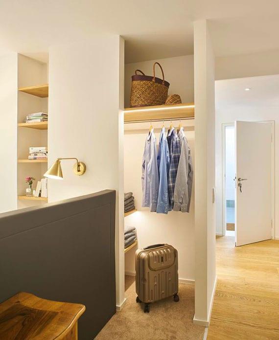 einraumwohnung einrichten mit doppelbett und kopfteil als niedriger trennwand, offener garderobe, holzbücherregal in wandnische