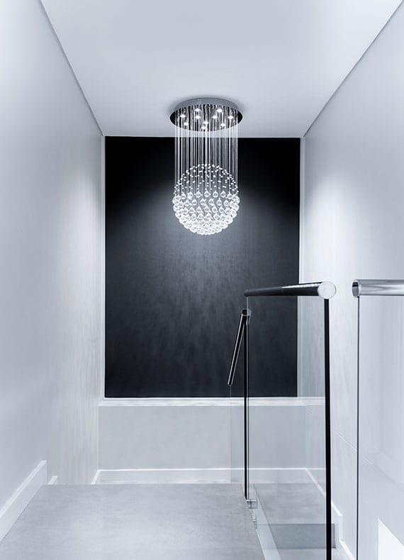 moderne gestaltungsideen innentreppe beton mit akzentwand schwarz, glasgeländer und moderne led leuchte als hänge-kugel-lampe