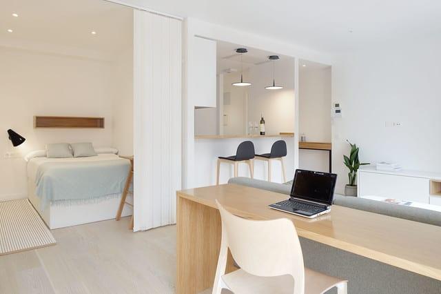einraumwohnung einrichten mit bürotisch hinterm sofa, schlafbereich mit doppel-hochbett hinter lamellenvorhang, kleiner wohnküche mit bartheke und barstühlen
