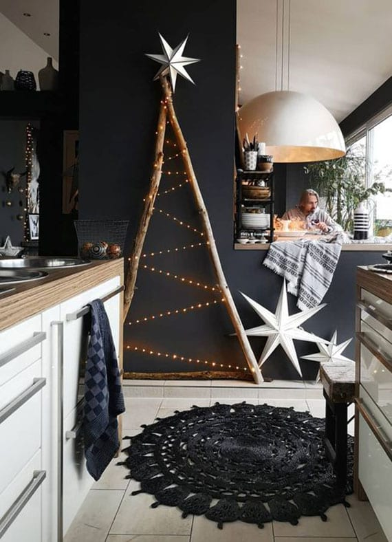 skandinavische weihnachtsdeko in der küche mit weißen sternen aus papier und diy weihnachtsbaum aus treibholz und lichterkette auf schwarzer wand