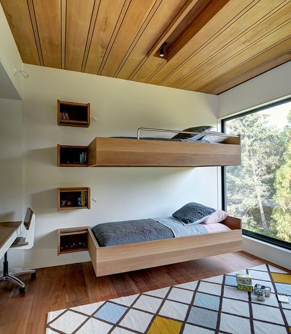 modernes kinderzimmer mit holzboden, holzdeckenverkleidung, modernem etagenbett aus holz mit holzregalen als treppenlösung und panoramafenster
