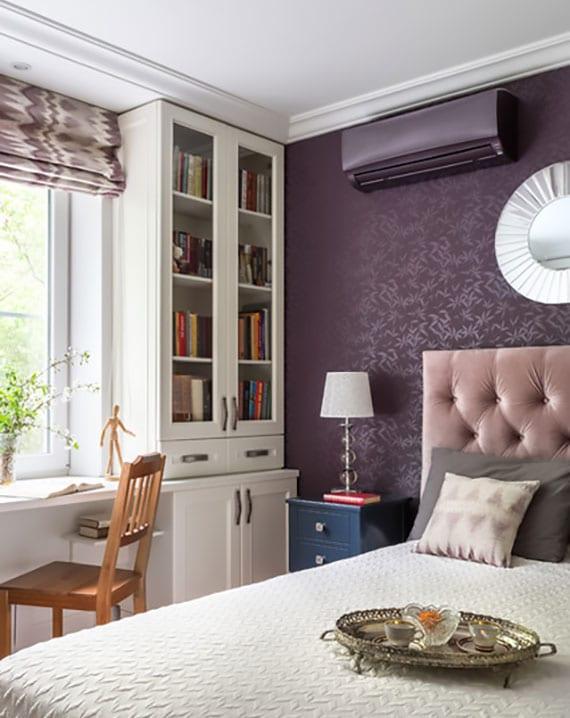 das kleine schlafzimmer elegant und gemütlich gestalten mit gemusterter wandtapete und klimaanlage in lila, fensterbank-schreibtisch, holzvitrine-bücherregal weiß und blauen nachttischen mit weißen tischlampen