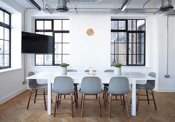 büroraum modern gestalten in weiß und schwarz mit parkettboden, schwarzen pfostenfenstern, besprechungstisch weiß und designer stühlen grau