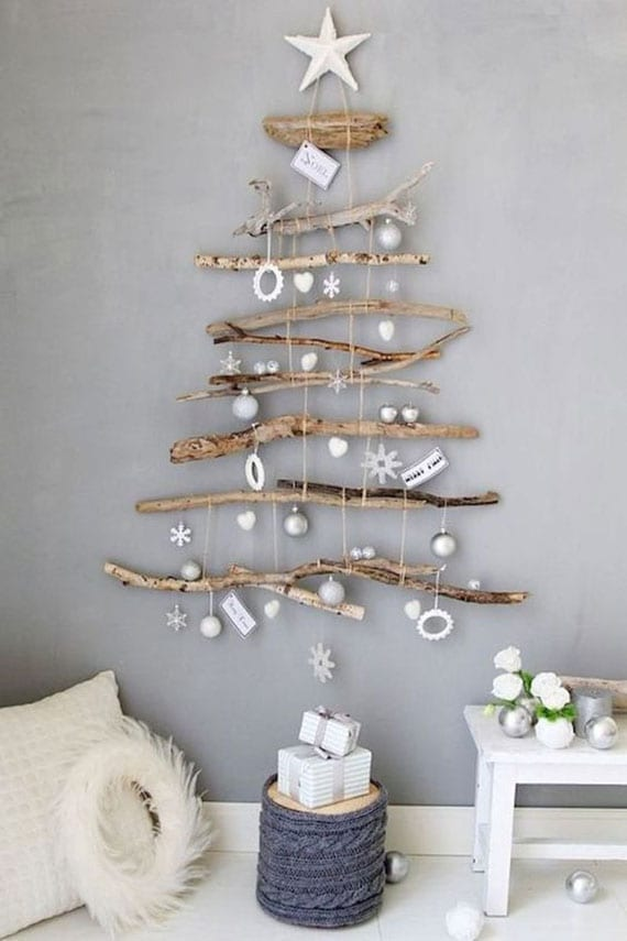 moderne zimmerdeko im skandinavischem stil mit diy weihnachtsbaum aus ästen, holzbeistelltisch weiß und weihnachtskranz aus weißen federn