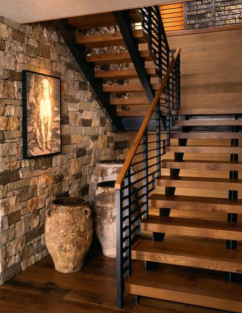 rustikale podesttrepe aus stahl mit holztreppenstufen als elegante geschossverbindung im modernem haus mit steinwandverkleidung und holzbodenbelag