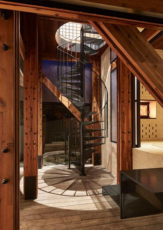 kreative raumgestaltung im rustikalen wohnstil mit schwarzem metall-spindeltreppe und sichtbarer holztragkonstruktion