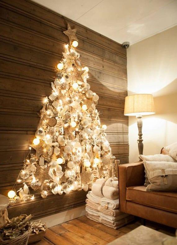 festliches Ambiente und fröhliche Weihnachtsstimmung schaffen mit einem DIY Weihnachtsbaum aus christbaumkugeln als leuchtende wanddeko im rustikalen wohnzimmer mit holzwandverkleidung