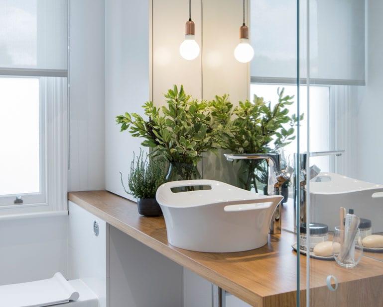 kleines bad mit fenster optisch vergrößern und stilvoll gestalten mit raumhohem spiegel hinter holzwaschtisch mit modernem aufsatzwaschbecken, grünen zimmerpflanzen und pendellampe