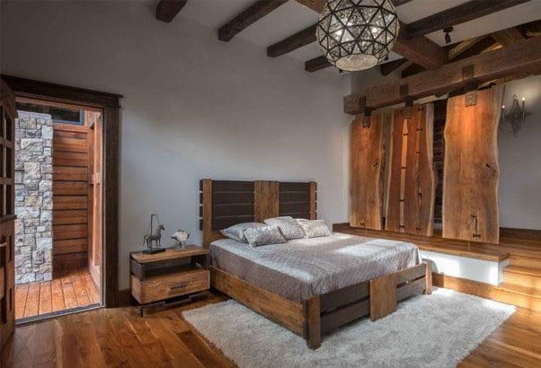 schlafzimmer im rustikalen stil mit doppelbet und nachtisch aus massivholz, holzbodenbelag und teppich grau, trennwand aus massivholzplatten