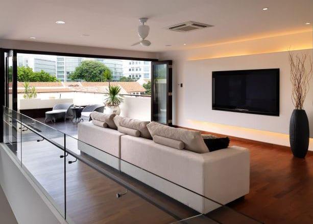 luxus-wohnzimmer interieur mit falttüren zur terrasse, TV-Wand weiß mit indirekter wandbeleuchtung vor 3er Sofa hellgrau