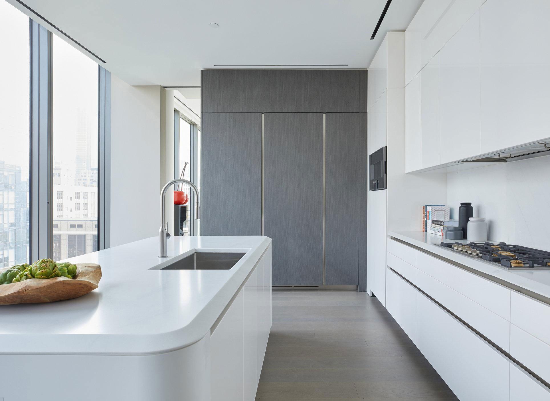 moderne einrichtung länglicher küche mit bodentiefen fenstern, weiße küchenschränken, corian-kücheninsel weiß
