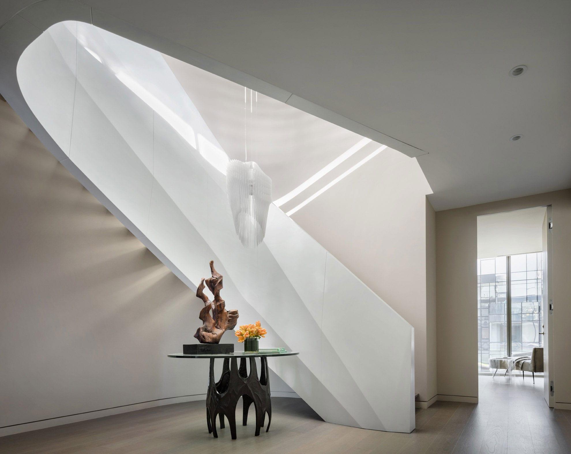 lichteffekte im raum durch attraktives treppen design einer innentreppe als skulpturale wendeltreppe mit weiß lackiertem metallgeländer