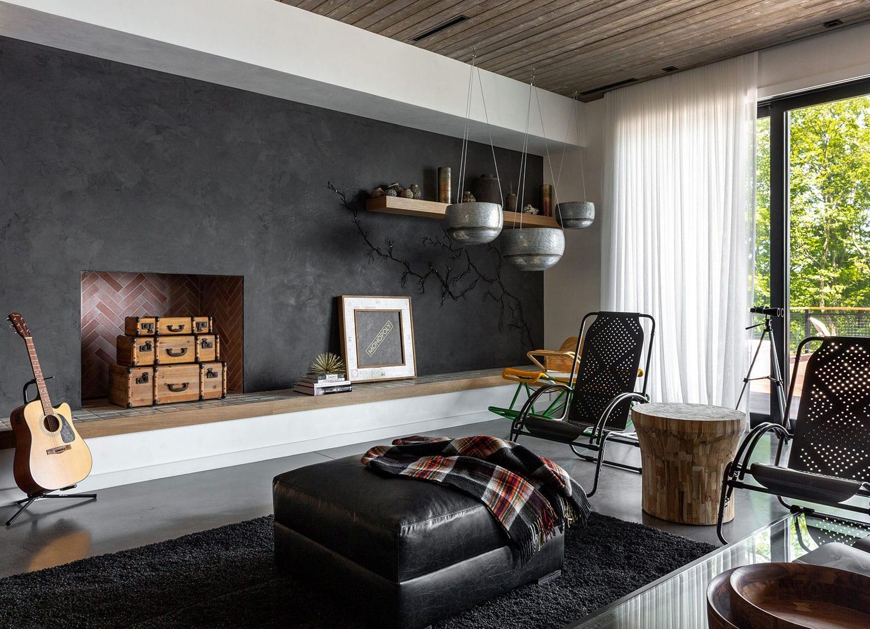 einrichtungstipps für das wohnzimmer_moderne raumgestaltung mit kamin, lowboard entlag akzentwand in schwarz, bodenbelag grau hochglanz, hochflorteppich schwarz, sessel-stühlen metall mit baumstamm-beistelltisch und lederhocker schwarz, weißen gardinen und holzdeckenverkleidung