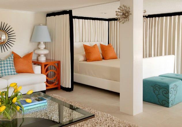 lebendige, attraktive und moderne raumgestaltungsidee für kleines wohnzimmer mit schlafbereich hinter gardinen, kuschelige sitzecke mit 2er-sofa weiß, glaskaffeetisch auf hochflorteppich beige, beistelltisch orange mit tischlampe, polsterhocker blau, wanddeko mit spiegel in sonnenrahmen