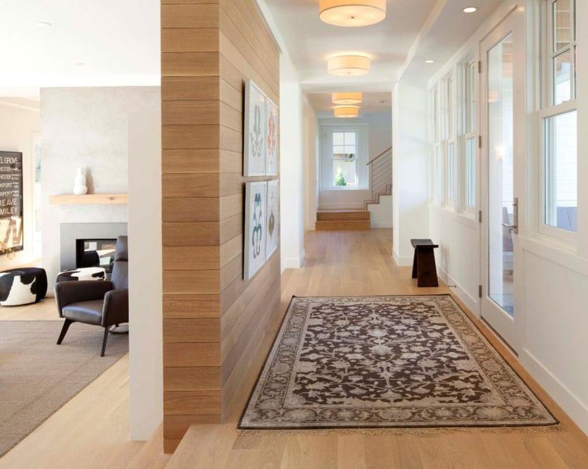 stilvolle raumgestaltung mit holzbodenbelag, wandfarbe weiß und holzakzentwand als trennwand zwischen flur und wohnzimmer mit kamin