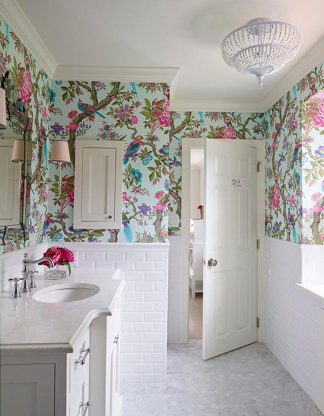 attraktive und moderne badezimmergestaltung in weiß mit metro-wandfliesen,hellblauer tapette mit buntem floral- und vogel-muster, klassischem holzwaschtisch weiß mit einbauwaschbecken oval, wandspiegel mit wandlampen im klassischen stil