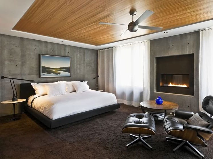 schlafzimmer einrichten tipps_schlafzimmer schön und gemütlich gestalten mit kamin, betonwänden, holzdeckenverkleidung, hochflorteppich braun, doppelbett mit kopfteil in grau, sitzecke mit rundem holztisch und eames sessel